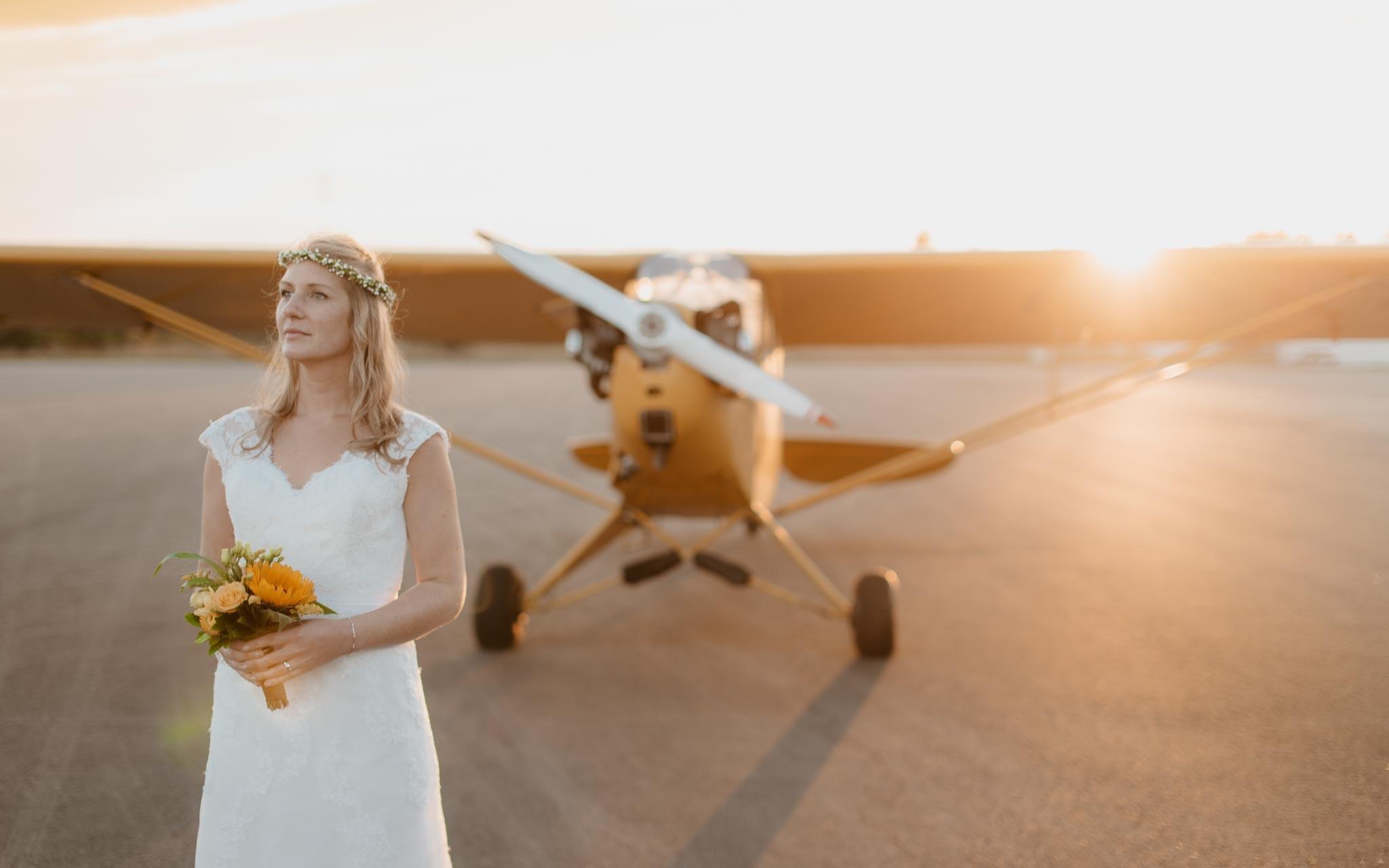 photo d'une mariée devant un avion biplace des années 40 lors d'une séance de couple day-after poétique & romantique sur le thème du voyage à l'aérodrome d'Ancenis par Geoffrey Arnoldy photographe
