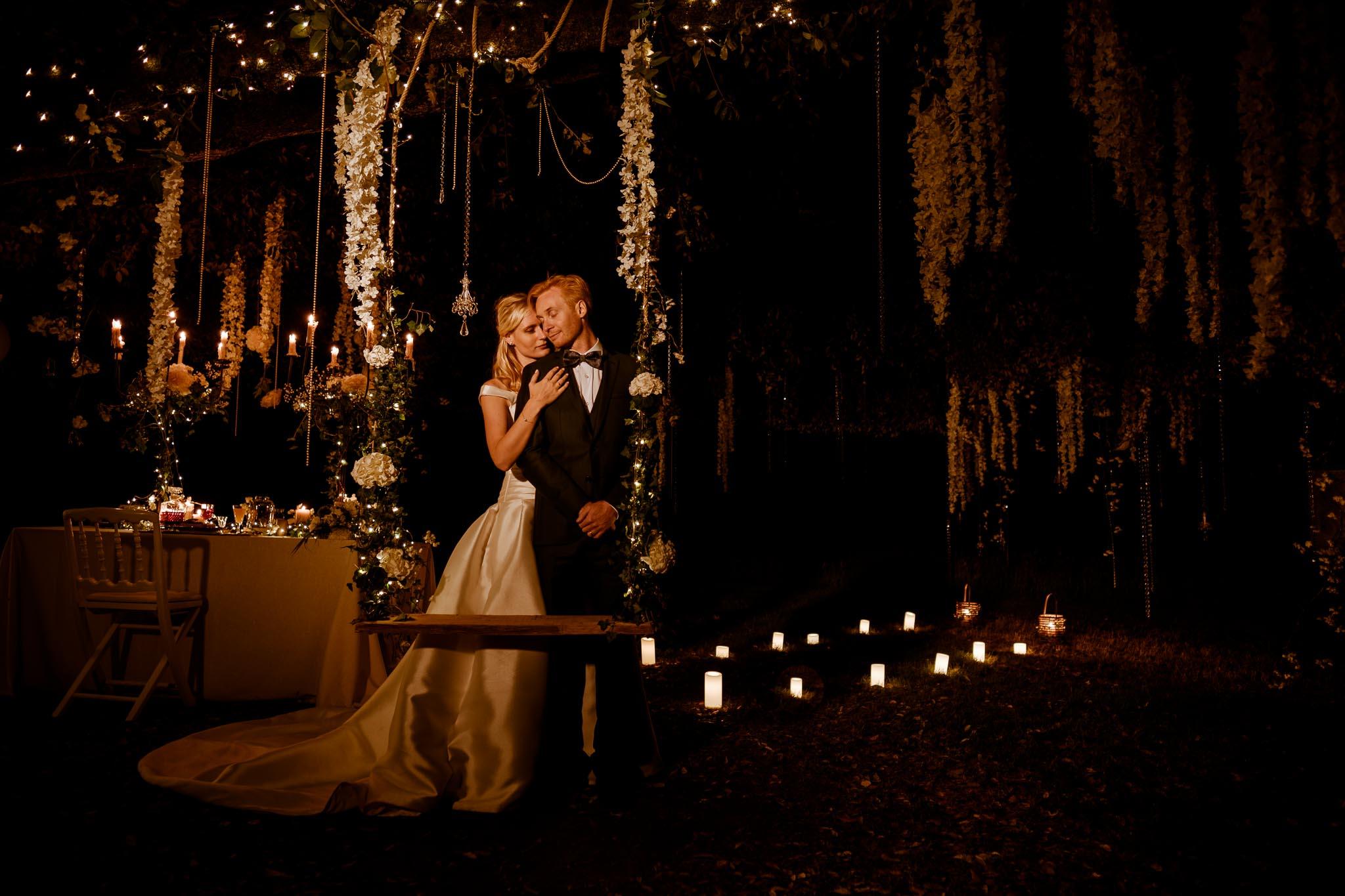 jeunes mariés près d'une balançoire dans les arbres, éclairés à la bougie sur une séance couple day-after au Château de Vair à Anetz par Geoffrey Arnoldy photographe